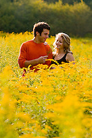 Couple embracing in field of goldenrod