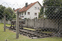 Germany. Bayern state. The Dachau Concentration Camp Memorial Site. A private house outside the camp and the camp fencing ( partly reconstructed in 1965) was made-up of grass, strips, ditches with an electrified barbed-wire fence and the camp wall. SS men guarded the camp grounds from seven towers. If a prisoner stepped onto the grass strip, he was shot at. Railway tracks. On march 22, 1933, the first concentration camp was opened in Dachau by the Nazis. It became a model for all later concentration camps established under the control of the SS men and the Third  Reich. © 2007 Didier Ruef