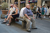 Man sitting on a bench in a street in Florence, Italy