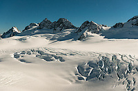Moonlight over mountain ranges of Southern Alps with Explorer Glacier crevasses in upper parts of Fox Glacier NEVE, Westland Tai Poutini National Park, West Coast, UNESCO World Heritage Area, New Zealand, NZ