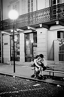 Switzerland. Canton Ticino. Bellinzona. Carnival. A young man is kissing an adolescent girl. Both teenagers are seated at night on a wood bench and are fallen in love. © 2007 Didier Ruef