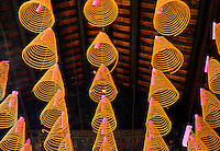 Conical incense coils hanging on wires below the roof at Chua Thien Hau Temple in Cho Lon, Ho Chi Minh City, Vietnam. Thien Hau Pagoda. Cholon, Ho Chi Minh City, Saigon<br />