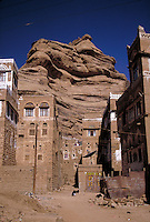 Painted, mud brick towerhouses line the streets of this small village, they have been constructed against the huge rock formation to the rear. buildings, dwellings. Qibla, Yemen.