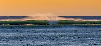 Large surf off Kawaihae Harbor with the mist lit up by the sunset on the Big Island.