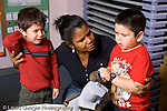 Education preschool female teacher working with two boys to settle conflict horizontal