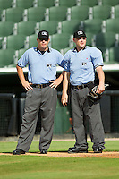 Umpires Cody Oakes (left) and Travis Godec chat between innings of the South Atlantic League game between the Greensboro Grasshoppers and the Kannapolis Intimidators at CMC-Northeast Stadium on July 13, 2013 in Kannapolis, North Carolina.  The Intimidators defeated the Grasshoppers 7-5.   (Brian Westerholt/Four Seam Images)
