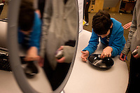 A boy looks at displays of concave mirrors presented by the Department of Physics at MIT's Under the Dome open house in Cambridge, Massachusetts, USA.