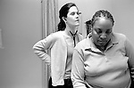 Young female internal medicine resident physician listening with stethoscope to back of middle age African-American female sitting on examination table