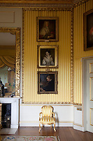 Portraits framed by gilded borders on the yellow drawing room walls