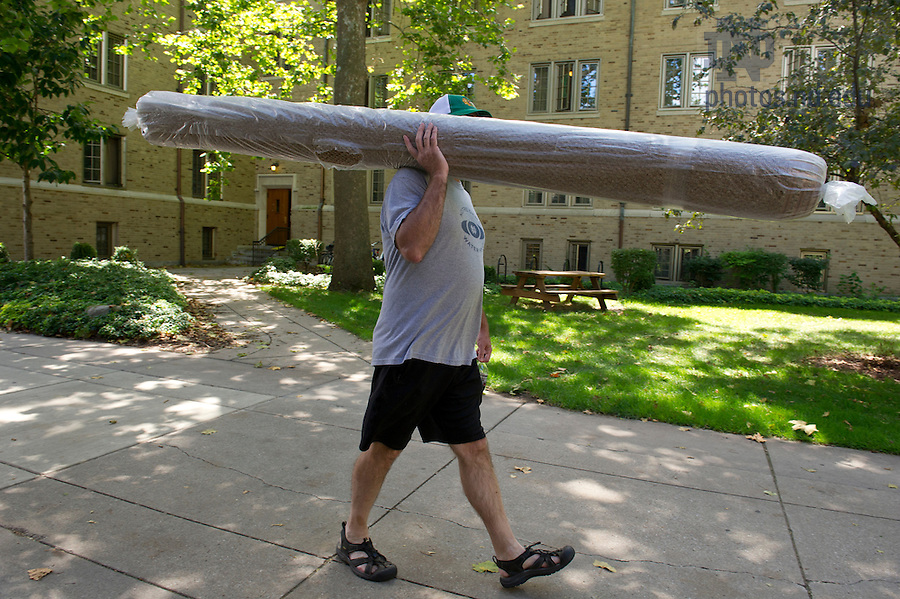 August 17, 2012; A father carries a rug across campus on move in day.  Photo by Barbara Johnston/University of Notre Dame