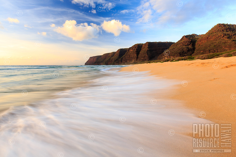 A soft wave fans out over the golden sand at Polihale Beach, Polihale State Park, Kaua'i.