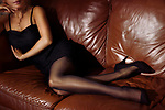 Closeup of legs of a sexy woman lying on a brown leather couch wearing a short black dress, stockings and high heels Image © MaximImages, License at https://www.maximimages.com