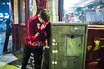 """© Joel Goodman - 07973 332324 . 16/12/2017. Manchester, UK. A man leans against a piece of street furniture for support , on Deansgate . Revellers out in Manchester City Centre overnight during """" Mad Friday """" , named for historically being one of the busiest nights of the year for the emergency services in the UK . Photo credit : Joel Goodman"""