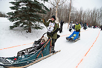 Fabio Berlusconi and team run past spectators on the bike/ski trail near University Lake with an Iditarider in the basket and a handler during the Anchorage, Alaska ceremonial start on Saturday, March 7 during the 2020 Iditarod race. Photo © 2020 by Ed Bennett/Bennett Images LLC