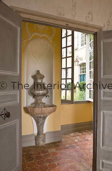 A grey marble drinking fountain has been built into a niche in the terracotta tiled entry hall