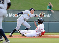 Infielder Dante Bichette, Jr. (19) of the Charleston RiverDogs stretches to reach a wide throw as Henry Ramos (51) of the Greenville Drive slides safely into third in a game on May 31, 2012, at Fluor Field at the West End in Greenville, South Carolina. Charleston won, 13-2. Bichette is the Yankees' No. 6 prospect, according to Baseball America and was a first-round draft pick in 2011. (Tom Priddy/Four Seam Images)
