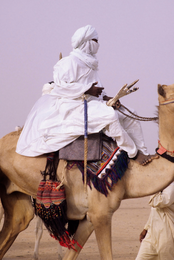 In-Gall, near Agadez, Niger - Tuareg Man Riding Camel, with Camel Saddle and Decorations Visible.  Man rides bare foot.  Camel has red leather talisman around his neck.