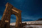 Stars and light clouds shine above the stone gate into Yellowstone National Park, Wyoming at night.