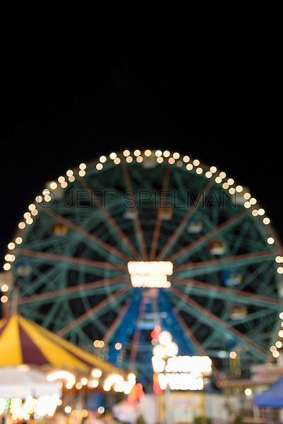 Defocused (Soft Focus) Night View of the Wonder Wheel (landmark ferris wheel) and amusement park at Coney Island, Brooklyn, New York City, New York State, USA