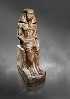 Ancient Egyptian statue of Wahka son of Neferhoptep, Middle Kingdom, 13th Dynasty, (1760 BC), Qaw el-Kebir, Tomb 7. Egyptian Museum, Turin. Grey background. <br /> <br /> This exceptional example of a private sculpture depicts a provincial official in almost Royal size and attitude. It was found inside the largest funerary chapel in Qaw el-Kebir, built of governor Wahka II around 1850 BC, The style indicates a date about a century later at a time when local governors did not build large tombs anymore. The statue was therefore installed by another Wahka into his ancestors chapel to keep the memory of his glorious lineage alive. Schiapelli excavations Cat 4265.