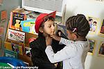 Education Preschool 3-4 year olds dressup pretend play girl helping boy wear jacket fastening it up for him