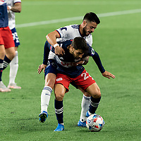 FOXBOROUGH, MA - APRIL 24: Carles Gil #22 of New England Revolution attempts to dribble as Junior Moreno #5 of D.C. United defends during a game between D.C. United and New England Revolution at Gillette Stadium on April 24, 2021 in Foxborough, Massachusetts.