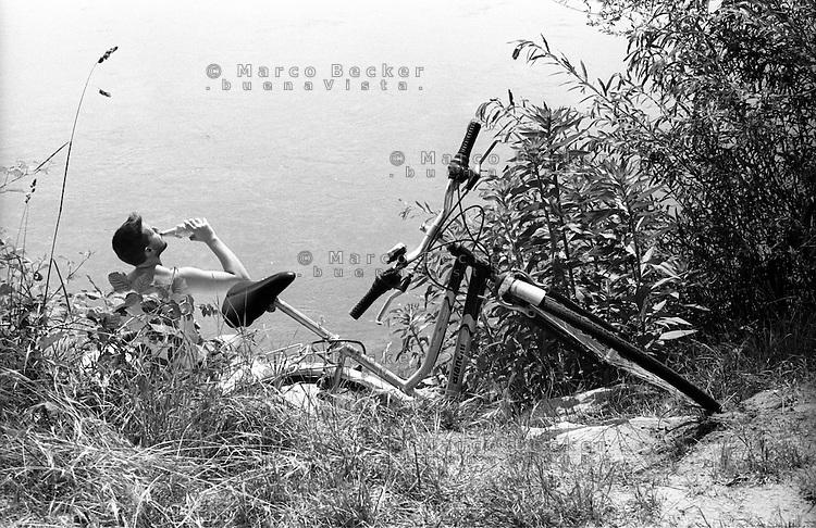 Parco del Ticino  presso Motta Visconti (provincia di Milano). Un ciclista prende il sole sulla riva del fiume e beve da una bottiglia --- Park of Ticino river near Motta Visconti (Province of Milan). A cyclist sunbathing on the riverbank and drinking from a bottle