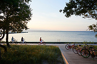 A family on a bicycle ride alongside the lake