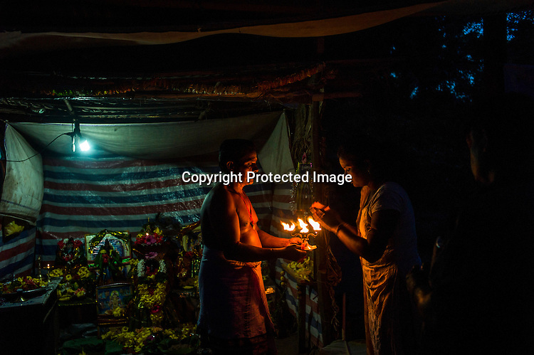Local Tamilians gather next to the priest offering prayers to the Hindu deity in a make-shift temple next to the actual temple destroyed during the war between the LTTE and the Sri Lankan army in Kilinochchi, in northern Sri Lanka. Photo: Sanjit Das/Panos