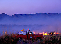 Fire fighters battle a desert grass fire with the Dos Cabezas Mountains in the background. Arizona.