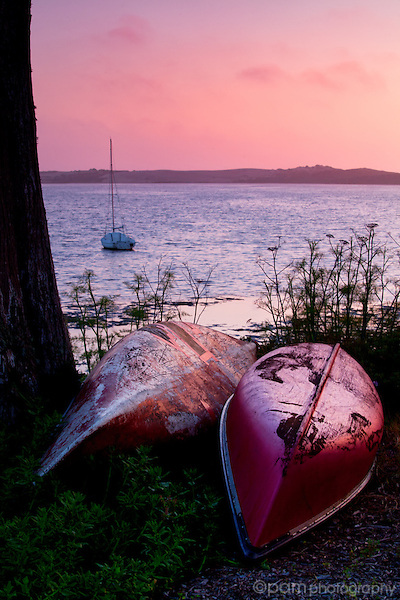 Two beached canoes and Morro Bay at sunset
