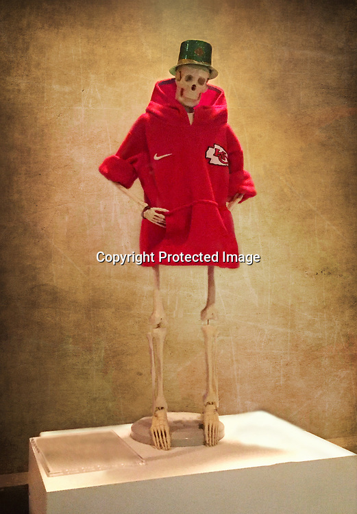A skeleton wearing Chiefs clothes stands against a wall.