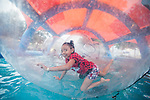 Isabella Galvan, 7, rides in a bubble during the NV150 Fair at Fuji Park in Carson City, Nev., on Sunday, August 3, 2014.<br /> (Photo By Kevin Clifford)