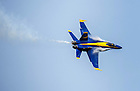 """Vapor trails or """"vapes"""" form on the leading edges of John Hiltz's jet.  The vapes are a sign of a 'high-G' maneuver where centrifugal force can make the pilot experience several times the normal force of gravity, sucking blood from the brain which if not dealt with can result in loss of consciousness.  The Blue Angels do not wear G-suits to combat this, instead relying on core strength training and anti-G muscle tightening techniques.  """"We're pulling between 7 and 8 Gs on a pretty regular basis…It's a physical demonstration,"""" says Hiltz.<br /> <br /> Photo by Matt Cashore/University of Notre Dame"""