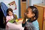 Education Preschool 4-5 year olds pretend play kitchen family area two girls playing separately one talking on the telephone horizontal