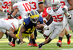 Michigan quarterback Denard Robinson (16) is tripped up by Ohio State defensive back C.J. Barnett, left, alongside defensive back Bradley Roby (25), in the fourth quarter of an NCAA college football game, Saturday, Nov. 26, 2011, in Ann Arbor. Michigan won 40-34. (AP Photo/Tony Ding)