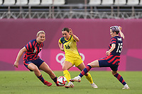 KASHIMA, JAPAN - AUGUST 5: Hayley Raso #16 of Australia is marked by Lindsey Horan #9 and Megan Rapinoe #15 of the United States during a game between Australia and USWNT at Kashima Soccer Stadium on August 5, 2021 in Kashima, Japan.