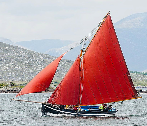 The spirit of the west – a re-juvenated Connemara Hooker making good speed to Kinvara against the distinctive background of The Burren