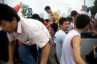 Spectators climb over a bridge railing in the rush to keep up with the Olympic torch during the Nanjing, China, leg of the 2008 Olympic Torch Relay.
