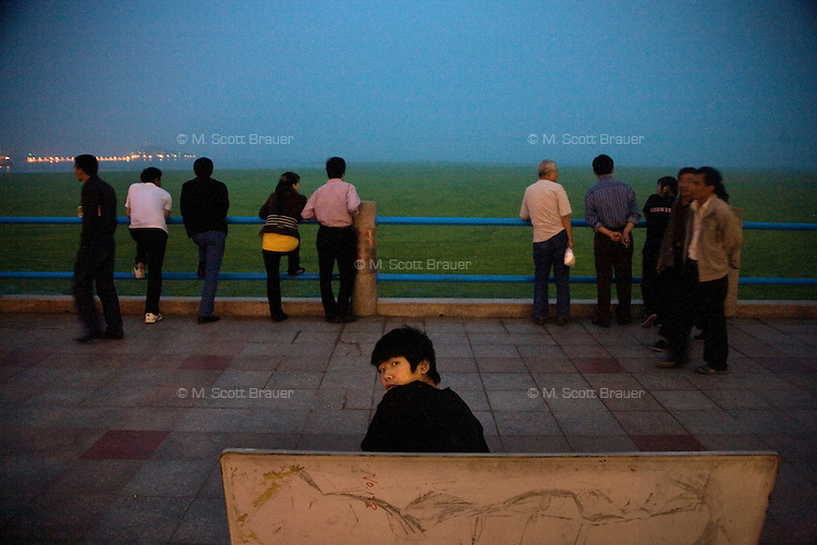 Tourists look over the algae covering Qingdao Bay in Qingdao, Shandong, China...Qingdao is the host of the sailing events for the 2008 Summer Olympics. Algae blooms like this have become common in inland lakes in China, often caused by high pollution in bodies of water.  The city is asking for help and forcing residents to take part in the cleanup effort before the Olympic events..