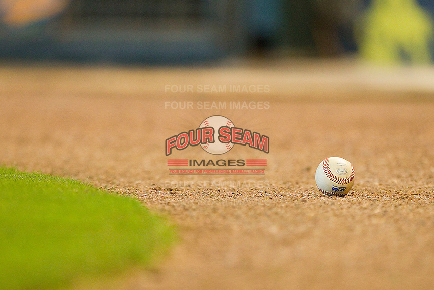 An NCAA baseball sits on the dirt behind home plate during the game between the Utah Utes and the Baylor Bears at Minute Maid Park on March 5, 2011 in Houston, Texas.  Photo by Brian Westerholt / Four Seam Images
