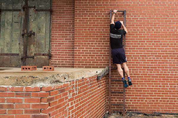 December 22, 2014. Lexington, North Carolina.<br />  Mayor Newell Clark uses his arms to climb a ladder at the abandoned Lexington Furniture factory.<br />  Newell Clark, the 43 year old mayor of Lexington, NC, leads a group of friends and colleagues on a 4 times a week exercise routine around downtown. The group uses existing infrastructure, such as an abandoned furniture factory, loading docks, stairs, and handrails to get fit and increase awareness of healthy lifestyles in a town more known for BBQ.<br /> Jeremy M. Lange for the Wall Street Journal<br /> Workout_Clark