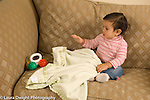 Ten month old baby girl looking for and finding hidden toy, pulling blanket off toy