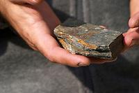 Rocks in the hand. Llicorella soil. Francesc Vernet Rigual, winemaker. Mas Igneus, Gratallops, Priorato, Catalonia, Spain.