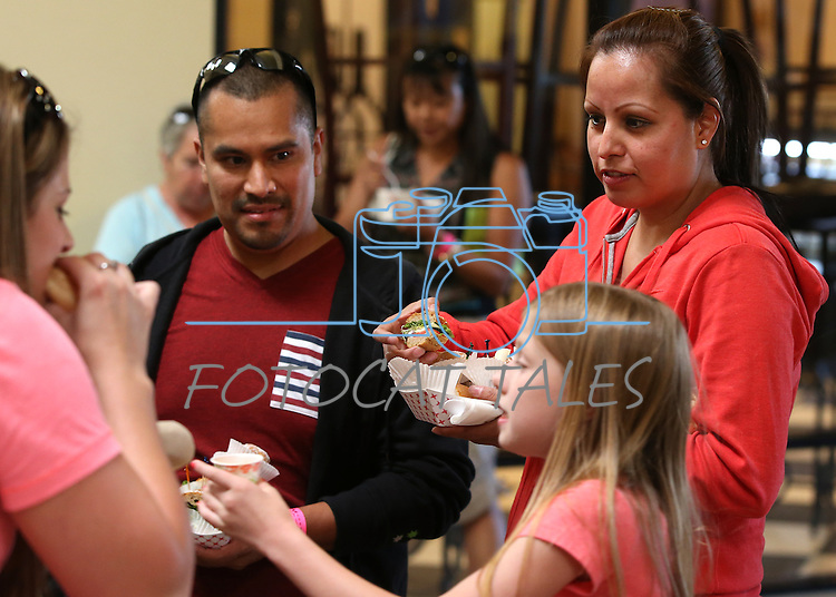 Oscar Corona and Mayra Ambriz eat at the Carson Mall during the 20th annual Taste of Downtown event in Carson City, Nev., on Saturday, June 15, 2013. The event features 44 local restaurants in a fundraiser for the Advocates to End Domestic Violence.<br /> Photo by Cathleen Allison