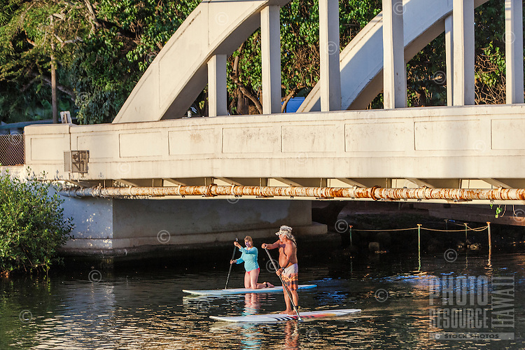 Older couple standup paddleboarding under Anahulu River Bridge in Haleiwa, O'ahu.