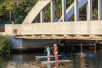 Older couple standup paddleboarding under Anahulu River Bridge in Haleiwa, O'ahu.