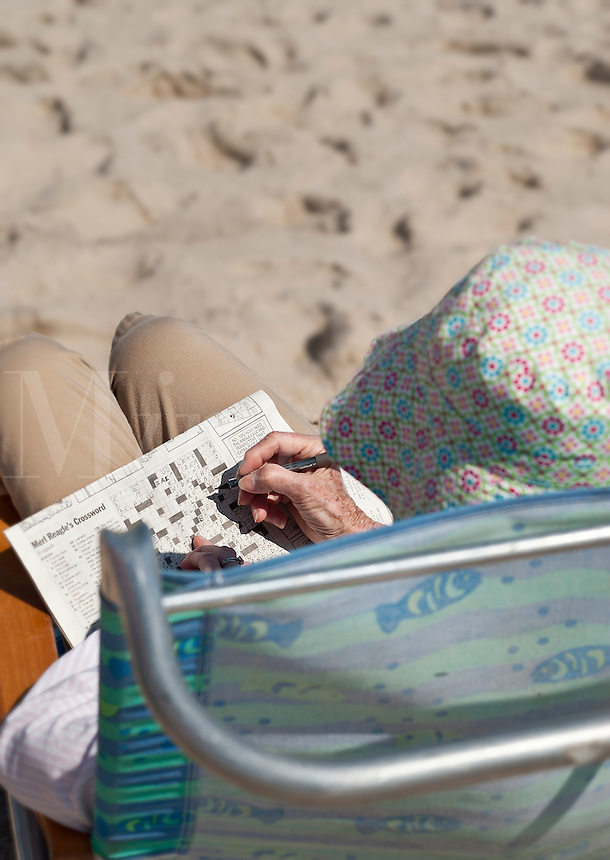 Mature woman at the beach with crossword puzzle.
