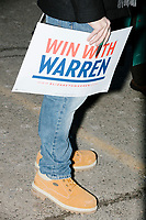 """A man holds a """"Win With Warren"""" campaign sign as Elizabeth Warren greets people after announcing her candidacy for the 2020 presidential election at Everett Mills, site of the 1912 Bread and Roses strike, in Lawrence, Massachusetts, USA, on Sat., Feb. 9, 2019."""