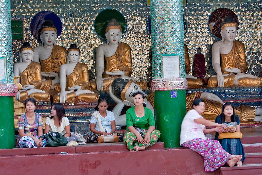 Myanmar, Burma.  Shwedagon Pagoda, Yangon, Rangoon.  Women Resting, Eating Snacks, on Steps of a Courtyard Shrine.  Behind them Buddha Statues  demonstrate the mudras (hand gestures) of earth-touching (bhumisparsha) and wisdom (dhyana).